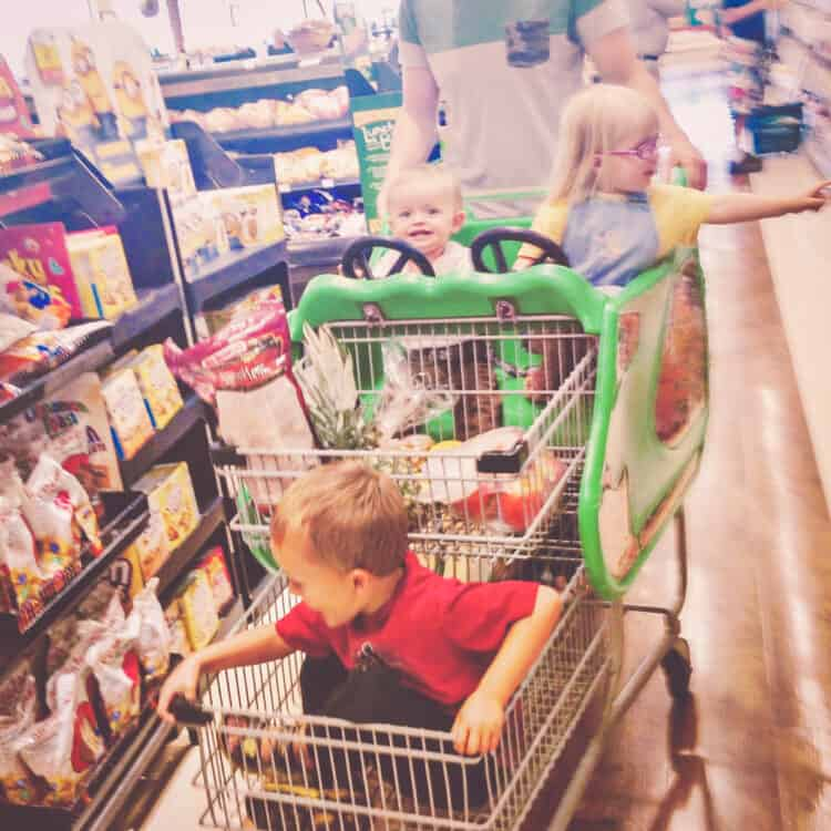three kids in one grocery cart