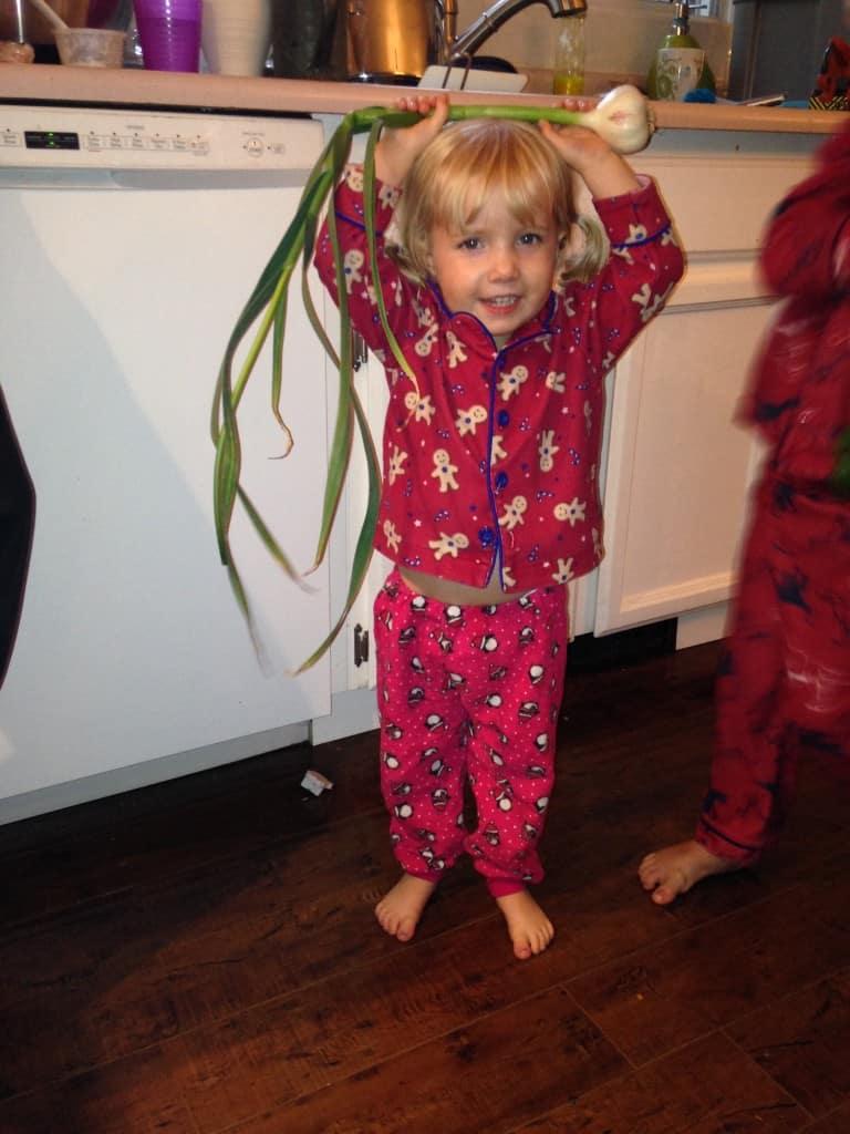 toddler with csa farm box garlic