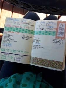 bullet journal in woman's lap. pages show a weekly layout with lists and errands listed in it how to plan your day step one: brain dump