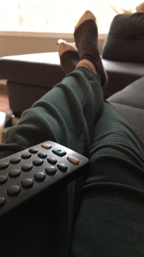 sitting with sweat pants and remote in hand