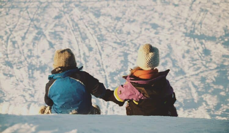 two kids sitting at the top of a sledding hill in the snow for simple christmas fun